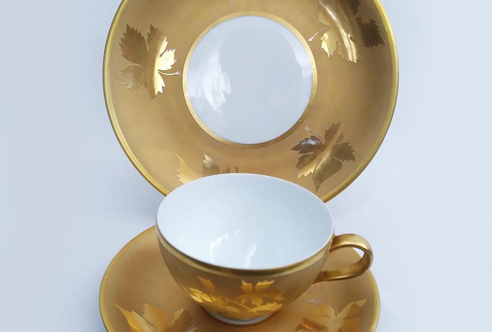 LO 113 – Trio: xícara antiga com prato de pão em porcelana Steatita dourada com folhas em relevo